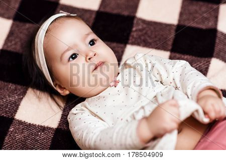 One year baby girl lying on the checkered plaid. Cute little baby girl.