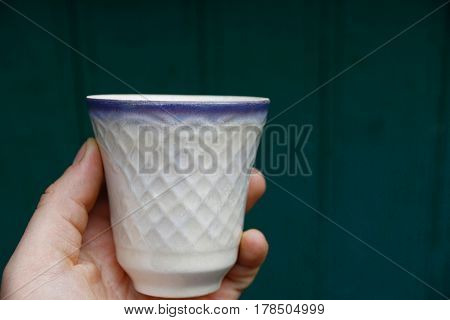 White cup in hand on a green background