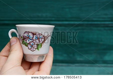 Hand holding a white cup with a pattern