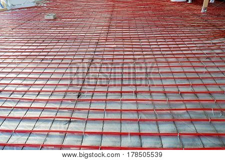 heated floor installation plastic tube attached to a metal grid