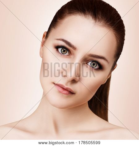 Beautiful young woman with clean skin and perfect makeup over beige background.