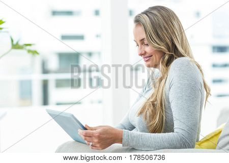 Pregnant woman sitting on sofa and using digital tablet