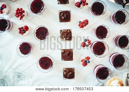 Tiramisu, traditional Italian dessert in glass on a white table. Panna cota. Look from above