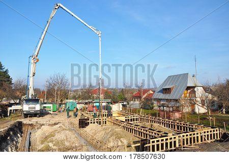 KIEV UKRAINE - March 28 2017:  Building a Foundation. Contractors making a concrete slab house foundation with car with pump tube. Pouring a concrete slab along the foundation