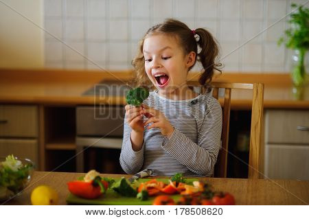 Girl of 8-9 years sits at a kitchen table. Before her various vegetables. In hands at child broccoli and red paprika. Girl is going to eat it. She has closed eyes from pleasure.