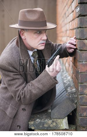 Mature gangster looking around a corner holding a gun