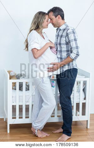 Portrait of pregnant couple holding baby shoes at home