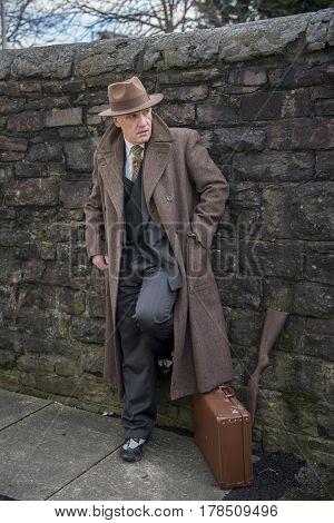 Mature man dressed as a 1940s gangster, with a shot gun.