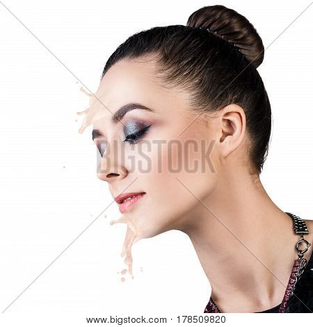 Young woman with beige foundation splashes and drops on face. Isolated on white.