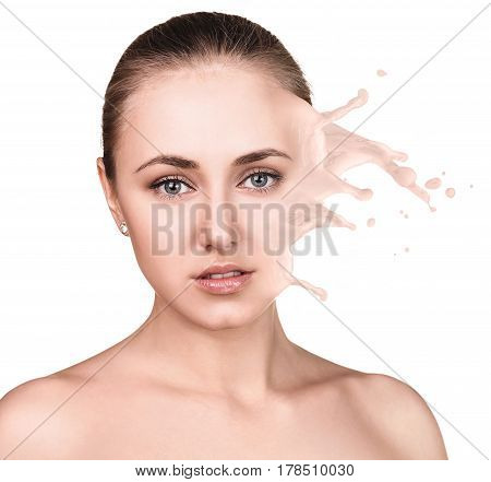 Young woman with beige foundation splashes and drops on face. Over beige background.