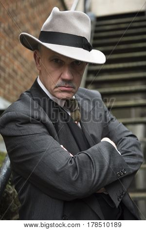Vertical image of a mature man dressed as a 1940s gangster, posing for the camera.