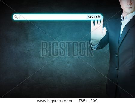 Businessman pushing digital searching button over dark wall background.