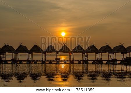 Floating Row of huts which rooftop made from dried leaf on the river during sunrise.
