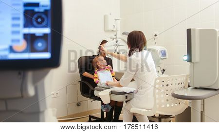 Optometrist in ophthalmology clinic checking little child's vision, wide angle
