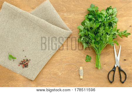 Bunch of parsley is on linen napkin on light brown wooden background. Focus is on the parsley. Copy-space composition