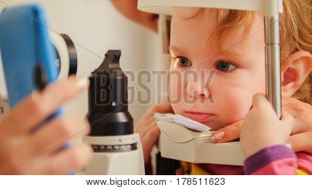 Child's optometry - little girl checks eyesight in eye ophthalmological clinic - close up, telephoto