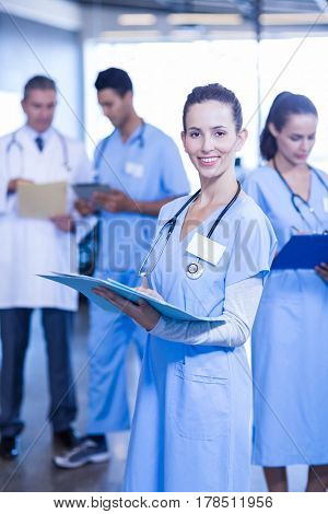 Female doctor holding medical report and smiling at camera while her colleagues standing in background