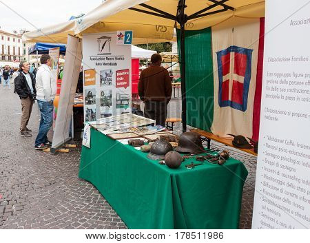 Verona Italy September 27 2015 : Table with explanations and items of weapons and work tools of the Second World War during the Sunday Fair in the Piazza Bra square in Verona Italy