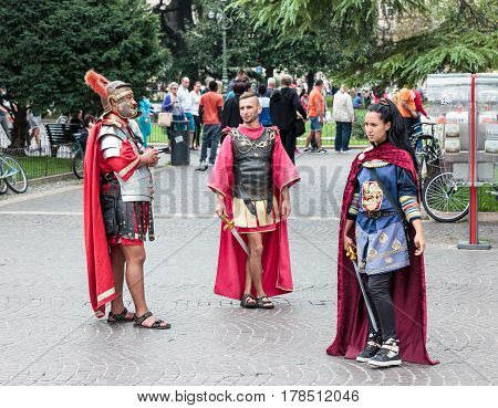 Verona Italy September 27 2015 : Two men and one woman dressed in the form of Roman legionaries stand at the Piazza Bra square near the Arena in Verona Italy