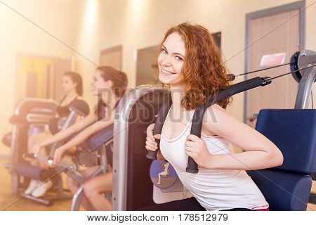 Young woman doing workout on exercise machine in gym