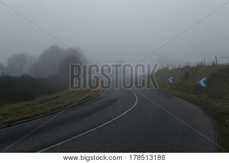 Foggy Asphalt Curved Road Passing Through The Forest. Weather With Low Visibility In The Region Of N
