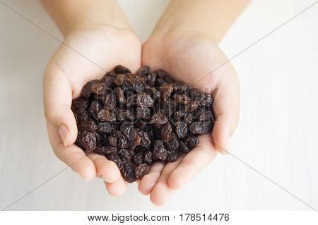 Child holding a handful of raisins on the white background.