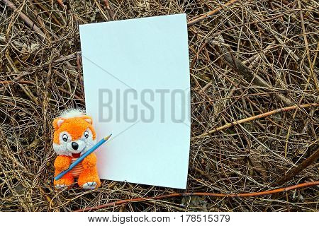 Soft toy with a pencil and a sheet of paper on dry plants
