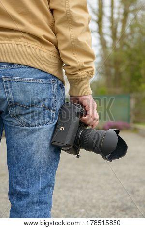 man photographer holding his photo camera outdoor