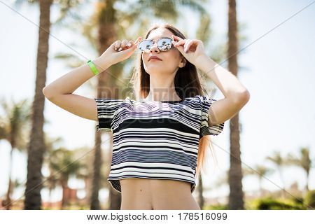 Woman Wearing Sunglasses On Eyes With Hands On Summer Resort On Palms Background. Summer Vocation.