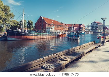 LITHUANIA KLAIPEDA - JULY 20 2016: Ships and boats on Dane river in oldtown of Klaipeda at summer day. Lithuania.