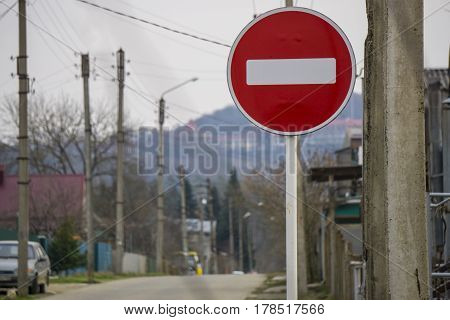 Round red road sign on metal pole. No Entry road-sign mounted on urban roadside.