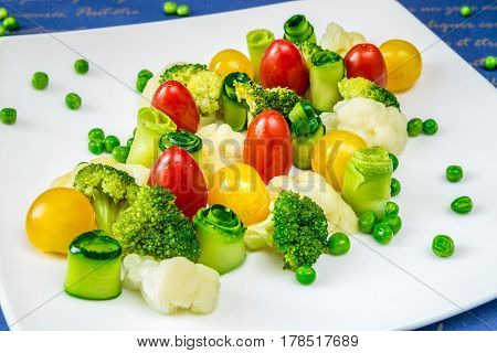 Vegetables tomatoes cucumbers peas and broccoli on a white plate