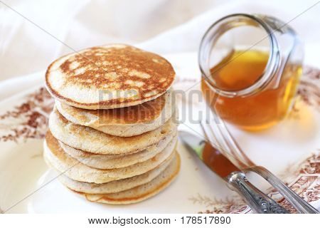 Heap of Pancake with honey on vintage plate