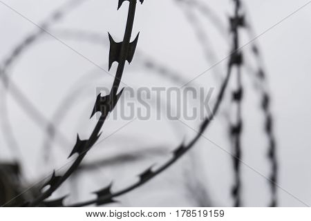 Barbed wire on dark fence. Silhouette photo.