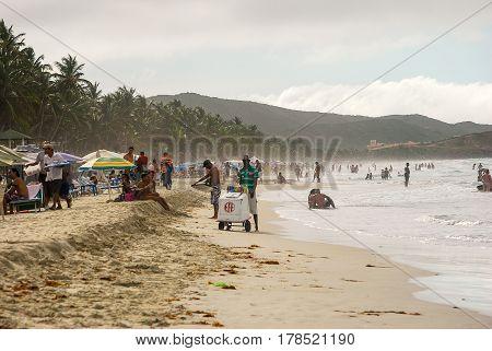 Playa el Agua,Venezuela-July 17,2011: An ice cream vendor stands by his cart among beachgoers on Playa el Agua on the Isla de Margarita
