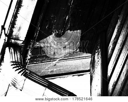 The web is under the roof of the old house. Black and white stylized photo