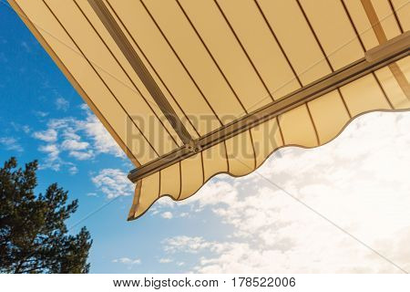 fabric awning against blue sunny summer sky