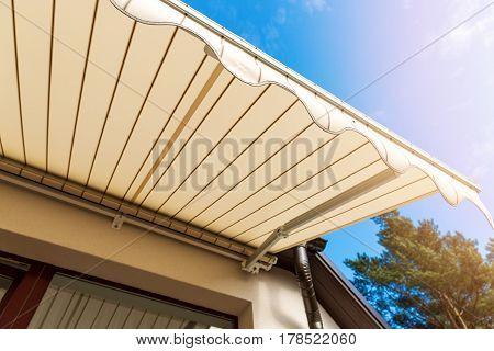 awning over balcony window against blue sky