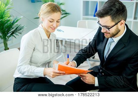 Two colleagues are discussing their work in office