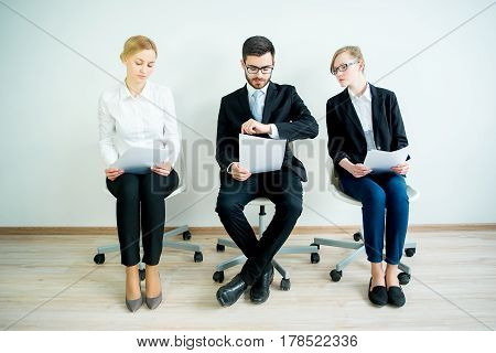 Three candidates are nervously waiting for a job interview