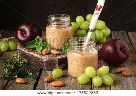 fruit smoothie plum banana grapes and nuts on a wooden background