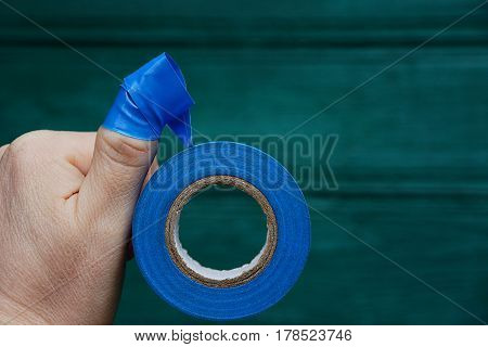 Blue insulating tape wound on the finger of the hand