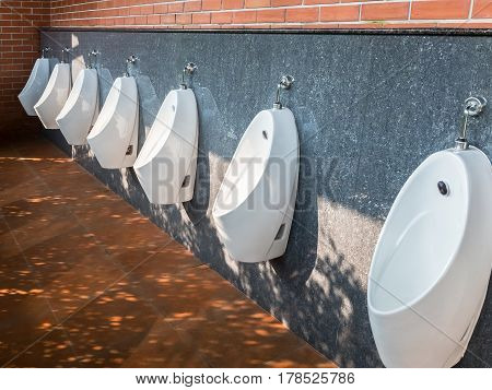 Modern urinals row in the back side of the clean public toilet.