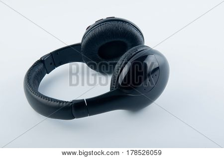 Modern black headphones lay on white background