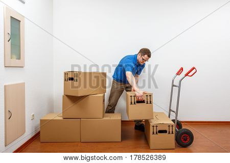 Man Is Packing Cartons On A Sack Barrow