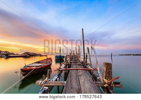Old wood bridge for small fishing boats in the sea with sunset