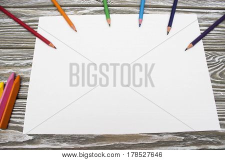 Clean sheet of paper with colors pencils on a wooden table. Mock up photo on timbered background.