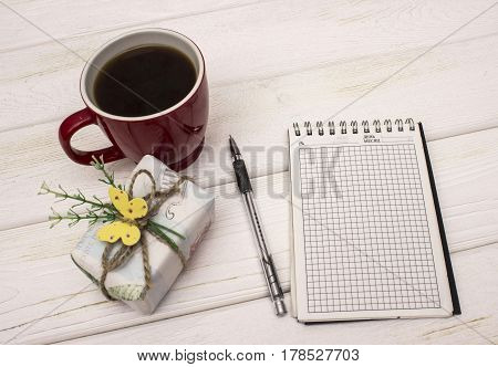 Notebook with coffee and gift box on a wooden table. Mock up photo on timbered background.