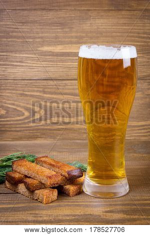Glass of lager beer and bread croutons on a wooden background