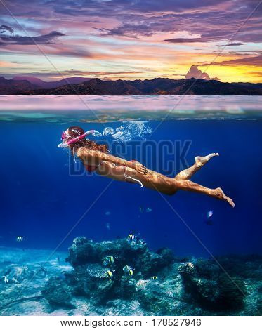 Underwater Shoot Of A Young Woman Snorkeling In A Tropical Sea And Colorful Sunset Splitted By Water